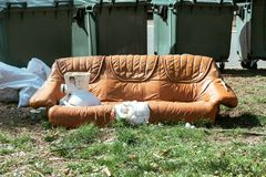 Sofá de couro obsoleto abandonado na rua foto de stock