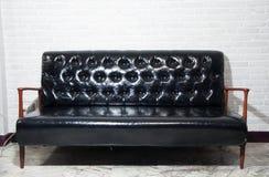Sofá de couro preto e cadeira de madeira do braço com fundo cinzento imagem de stock