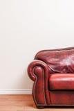 Sofá de couro vermelho luxuoso na frente de uma parede vazia Fotos de Stock Royalty Free