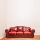 Sofá de couro vermelho luxuoso na frente de uma parede vazia Imagem de Stock