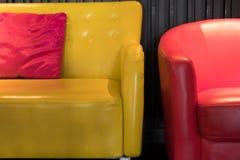 sofá de cuero amarillo con la almohada rosada de la tela y la butaca roja Fotos de archivo libres de regalías
