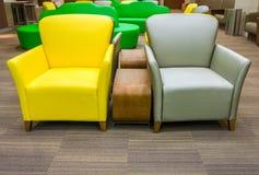 Sofá de cuero amarillo y gris con la tabla de madera lateral Foto de archivo libre de regalías
