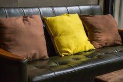 Sofá de cuero con la cafetería de los amortiguadores imagen de archivo libre de regalías