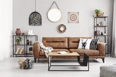 Sofá de cuero con las almohadas y la manta en la sala de estar elegante interior con los estantes del metal y la mesa de centro m foto de archivo