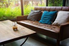 Sofá de cuero con un vidrio de agua en una tabla de madera en un café fotografía de archivo