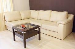 Sofá de cuero de la esquina blanco moderno y tabla de madera Foto de archivo