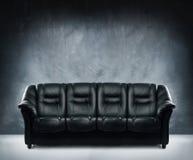 Sofá de cuero negro en interior dramático Foto de archivo libre de regalías