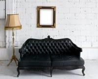 Sofá de cuero negro viejo con la lámpara Fotos de archivo