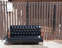 Sofá de cuero negro y silla de madera de los apoyabrazos con el buzón blanco en fondo marrón imagen de archivo