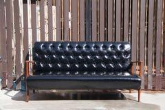 Sofá de cuero negro y silla de madera de los apoyabrazos con el fondo marrón foto de archivo