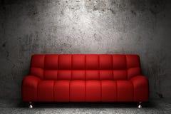 Sofá de cuero rojo delante de la pared del grunge Fotos de archivo libres de regalías