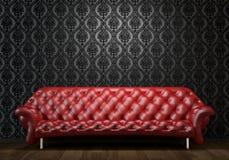 Sofá de cuero rojo en la pared negra Imagen de archivo