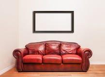 Sofá de cuero rojo lujoso delante de una pared en blanco Imágenes de archivo libres de regalías