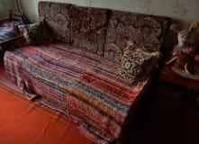 Sofá de Ethno con la colcha hecha punto fotografía de archivo