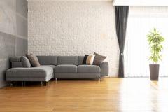 Sofá de la esquina gris en piso de madera contra la pared de ladrillo en a brillante imagen de archivo libre de regalías