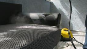 Sofá de la limpieza con un vapor de un agua más limpia del vapor de un profesional Concepto casero almacen de metraje de vídeo