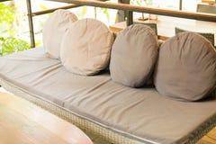 sofá de mimbre con el amortiguador y la almohada marrones Foto de archivo libre de regalías
