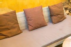 sofá de mimbre con el amortiguador y la almohada marrones Imagen de archivo libre de regalías