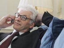 Sofá de Using Cellphone On del hombre de negocios imagenes de archivo
