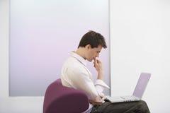Sofá de Using Laptop On del hombre de negocios imagen de archivo