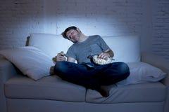 Sofá del hombre joven en casa en la sala de estar que duerme mientras que mira película o deporte en la TV en la noche Fotografía de archivo libre de regalías