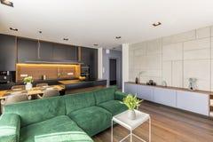 sofá del terciopelo colocado en interior de la sala de estar y de la cocina del espacio abierto con las flores frescas, la mesa d foto de archivo libre de regalías