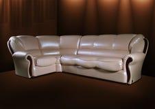 Sofá do couro branco em um fundo marrom Fotografia de Stock Royalty Free
