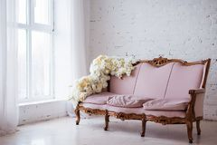 Sofá do estilo do vintage decorado com as flores na sala interior do sótão com janela grande imagem de stock royalty free
