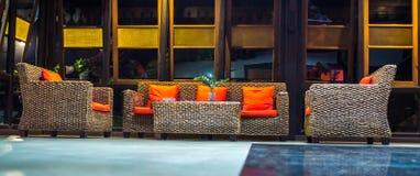 Sofá do Rattan com o coxim alaranjado na entrada de um hotel imagem de stock royalty free