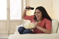 Sofá do sofá da mulher em casa que olha o esporte entusiasmado do futebol da tevê comemorar a vitória Fotografia de Stock