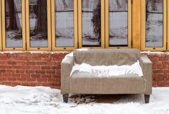Sofá en la nieve cerca de una pared de ladrillo con las ventanas Fotos de archivo