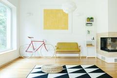Sofá entre la bicicleta y el estante Imagen de archivo libre de regalías