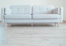 Sofá escandinavo contemporáneo acogedor del estilo en el suelo de la lamina del roble imagen de archivo