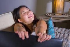 Sofá feliz y relajado de la muchacha china asiática hermosa joven del estudiante en casa del sofá usando Internet en looki del es imágenes de archivo libres de regalías
