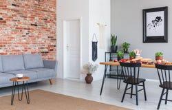 Sofá gris contra la pared de ladrillo roja en interior plano con el cartel y sillas negras en la mesa de comedor Foto verdadera fotografía de archivo