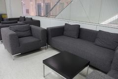 Sofá gris oscuro de la tela en la sala de espera o la oficina contemporánea internacional Imagenes de archivo