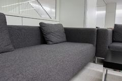 Sofá gris oscuro de la tela en la sala de espera o la oficina contemporánea internacional Fotos de archivo