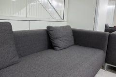 Sofá gris oscuro de la tela en la sala de espera o la oficina contemporánea internacional Fotos de archivo libres de regalías