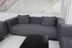 Sofá gris oscuro de la tela en la sala de espera o la oficina contemporánea internacional Imágenes de archivo libres de regalías
