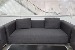 Sofá gris oscuro de la tela en la sala de espera o la oficina contemporánea internacional Fotografía de archivo libre de regalías