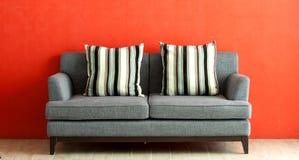 Sofá gris puesto en el estuco rojo Fotografía de archivo