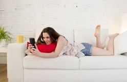 Sofá hermoso joven de la muchacha en casa relajado usando la sonrisa del teléfono móvil feliz y alegre Foto de archivo