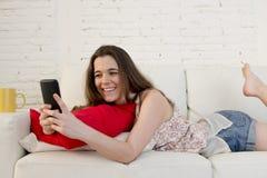 Sofá hermoso joven de la muchacha en casa relajado usando la sonrisa del teléfono móvil feliz y alegre Fotos de archivo
