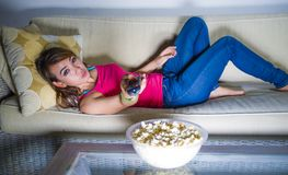 Sofá latin latino-americano feliz novo do sofá da mulher em casa que olha o telefone foto de stock