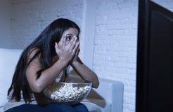 Sofá latino del sofá de la mujer en casa en película de terror de la televisión de la sala de estar o novela de suspense asustadi foto de archivo