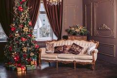 Sofá lujoso en el interior Celebración del Año Nuevo Árbol de navidad adornado con juguetes y una guirnalda Imagen de archivo libre de regalías
