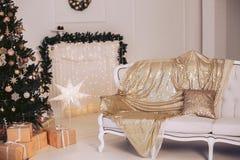 Sofá lujoso en un interior del ` s del Año Nuevo con un árbol de navidad adornado con juguetes y una guirnalda Imagen de archivo