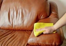 Sofá marrón de limpieza con un paño amarillo Fotografía de archivo libre de regalías