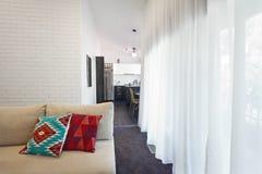 Sofá moderno de la sala de estar y cortinas escarpadas horizontales Imagen de archivo libre de regalías