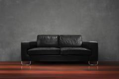 Sofá negro con el muro de cemento de madera del piso en sala de estar vacía Fotografía de archivo libre de regalías